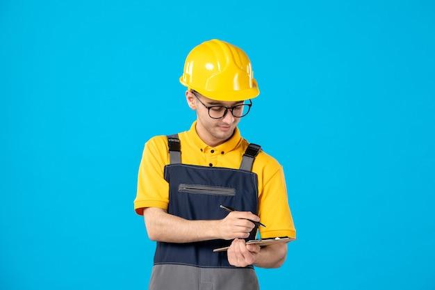 Vue de face travailleur masculin en uniforme jaune en prenant des notes sur le bleu