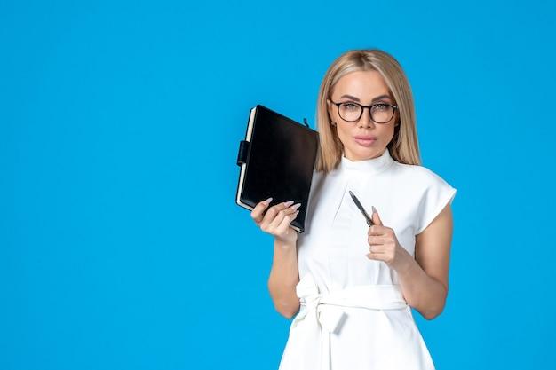 Vue de face d'une travailleuse en robe blanche posant avec un bloc-notes sur un mur bleu