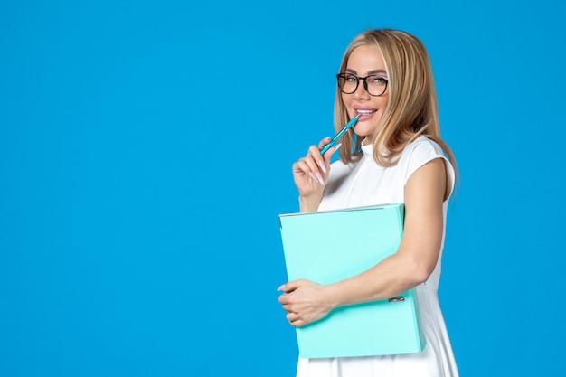 Vue de face d'une travailleuse en robe blanche tenant un dossier bleu sur un mur bleu
