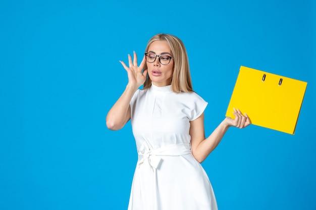 Vue de face d'une travailleuse en robe blanche tenant un dossier jaune sur un mur bleu