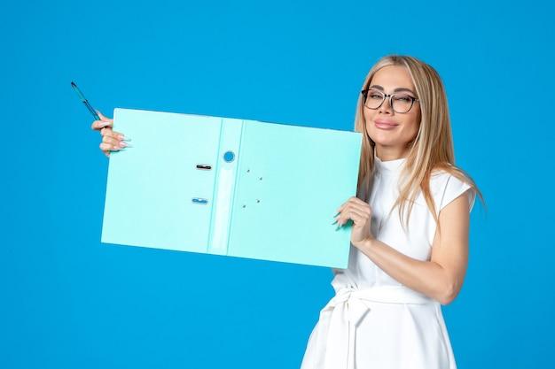 Vue de face d'une travailleuse en robe blanche tenant un dossier ouvert sur un mur bleu
