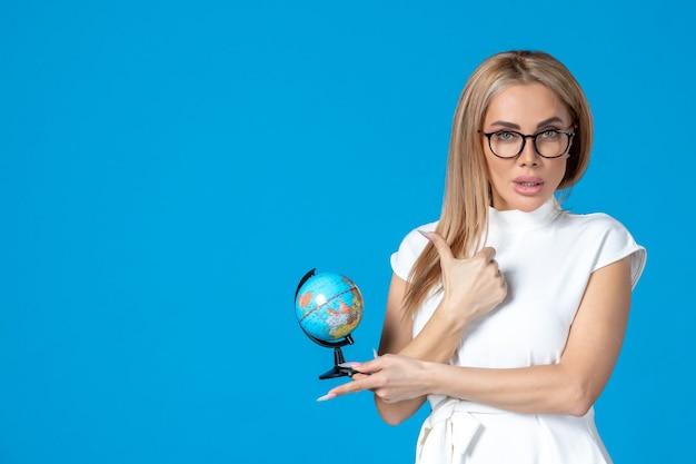 Vue de face d'une travailleuse en robe blanche tenant un petit globe terrestre sur un mur bleu