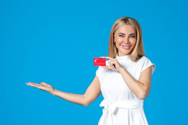 Vue de face d'une travailleuse tenant une carte bancaire rouge sur un mur bleu