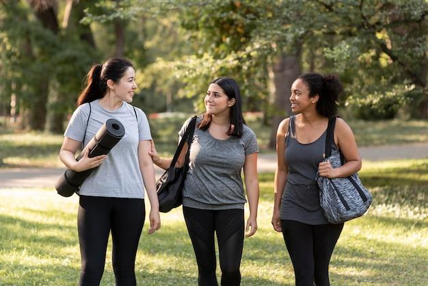 Vue de face de trois amies dans le parc