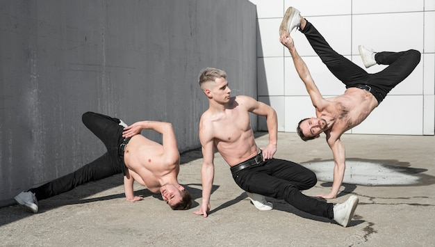 Vue de face de trois artistes hip hop torse nu dansant