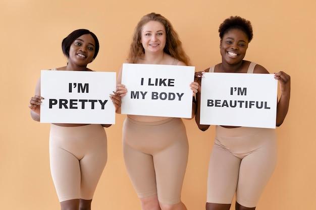 Vue de face de trois femmes tenant des pancartes avec des déclarations de positivité du corps