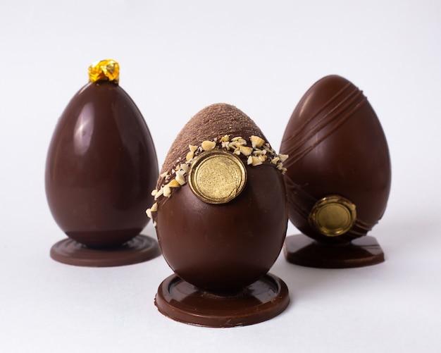 Vue de face trois œufs en chocolat décorés avec des noix et de l'or sur support