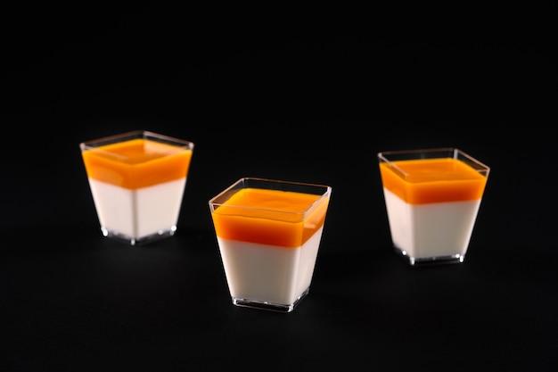 Vue de face de trois petits verres carrés avec panna cotta laiteuse décorée d'une garniture orange vif. dessert délicieux sucré isolé sur fond de studio noir. concept alimentaire.