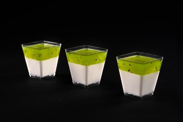 Vue de face de trois petits verres carrés avec panna cotta laiteuse. délicieux dessert sucré décoré de garniture de pomme vert vif, isolé sur fond noir. concept alimentaire.