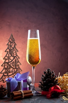 Vue de face verre de champagne avec cadeau et jouets sur boisson légère alcool photo couleur champagne nouvel an