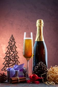 Vue de face verre de champagne avec cadeaux et bouteille sur boisson légère alcool photo couleur champagne nouvel an