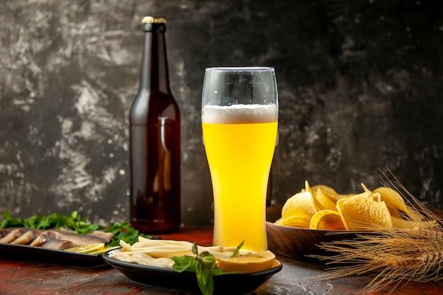 Vue de face verre d'ours avec des cips au fromage et du poisson sur une photo sombre collation couleur vin alcool viande