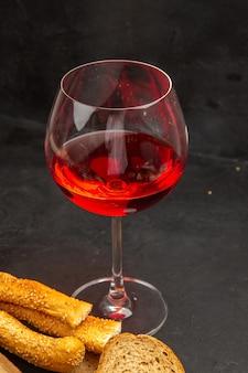 Vue de face verre de vin avec des petits pains et du pain sur une photo d'alcool de bière de couleur foncée
