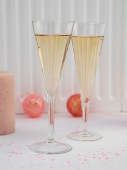 Vue de face de verres de champagne et de globes roses