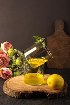 Une vue de face verres avec jus de jus de citron à l'intérieur de verres transparents le long de citron entier et de fleurs sur le bureau en bois brun et fond gris cocktail citron