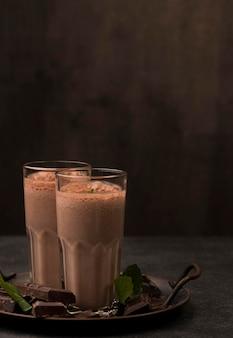 Vue de face des verres de milkshake avec du chocolat et de l'espace de copie