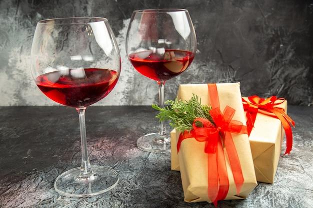 Vue de face des verres de vin cadeaux de noël sur dark