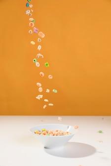 Vue de face versant des céréales sur le bol de la table
