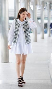 Vue de face verticale portrait complet du corps d'une jolie jeune femme asiatique adulte souriante aux cheveux bruns, des vêtements modernes à la mode et des chaussures à talons hauts, marchant vers la rue et regardant la caméra