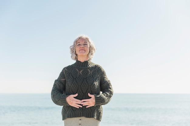 Vue de face vieille femme aux yeux fermés sur la plage