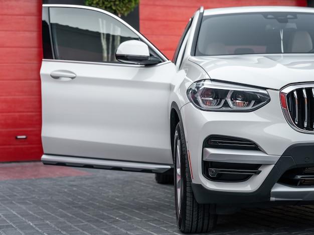 Vue de face d'une voiture suv moderne de couleur blanche avec porte d'entrée passager ouverte.
