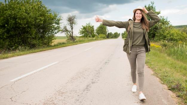 Vue de face voyageur élégant faisant de l'auto-stop