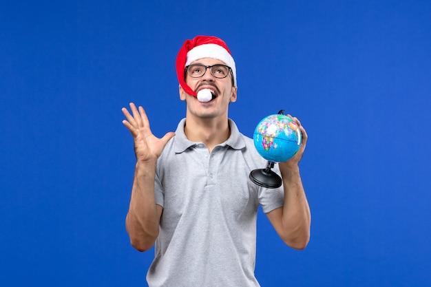 Vue de face young male holding globe terrestre sur les avions mur bleu voyage de vacances mâle