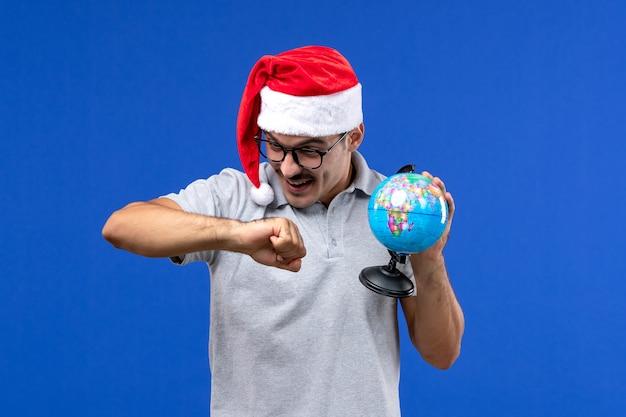 Vue de face young male holding globe terrestre sur mur bleu voyage avions vacances mâle