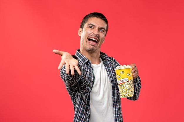 Vue de face young male holding pop-corn avec une expression inquiétante sur le mur rouge clair cinéma films cinéma mâle