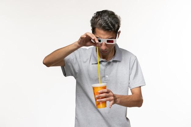 Vue de face young male holding soda dans des lunettes de soleil sur le mur blanc à distance le plaisir du film solitaire