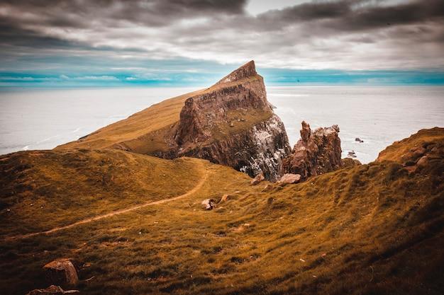 Vue sur les falaises et la côte sur la mer de l'île de mykines