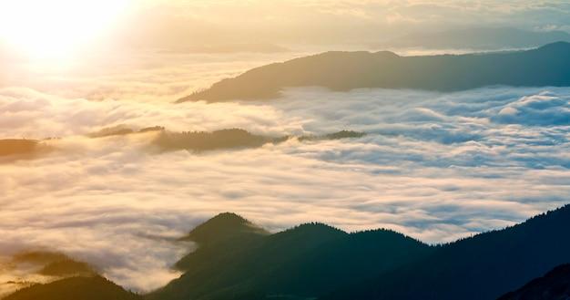 Vue fantastique sur la vallée de montagne recouverte de bas bouffants blancs comme des nuages de neige s'étendant jusqu'à l'horizon brumeux sous un ciel matinal lumineux avec une lueur orange clair au lever du soleil. beauté du concept de la nature.
