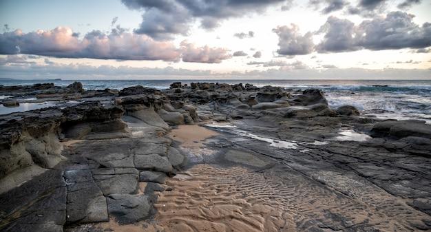 Vue fascinante sur le coucher de soleil sur le littoral rocheux de kap geinitzort à rostock, allemagne