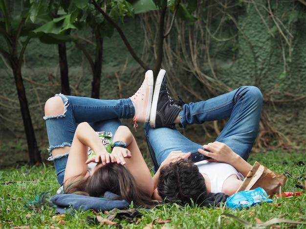Vue fascinante d'un joli couple allongé sur l'herbe dans la forêt