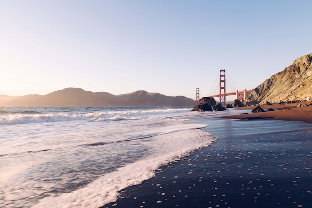 Vue fascinante sur l'océan calme avec le pont et les montagnes en arrière-plan, usa