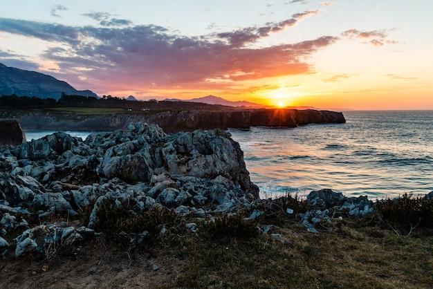 Vue fascinante sur l'océan calme et les rochers près du rivage au coucher du soleil