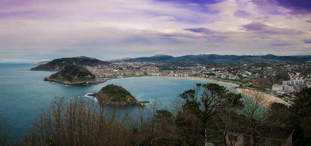 Vue fascinante de la ville le long de la côte par une journée nuageuse avec une nature luxuriante
