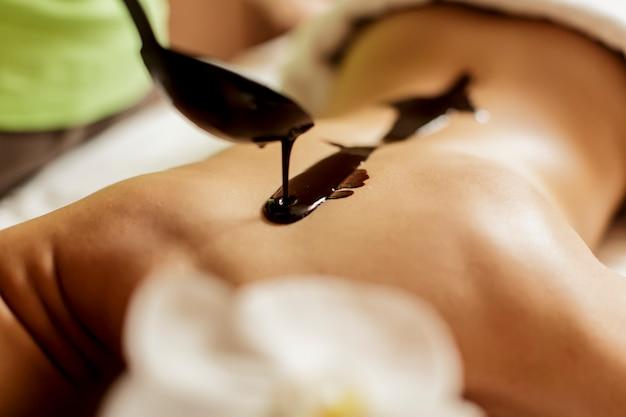 Vue à la femme ayant un massage au chocolat chaud