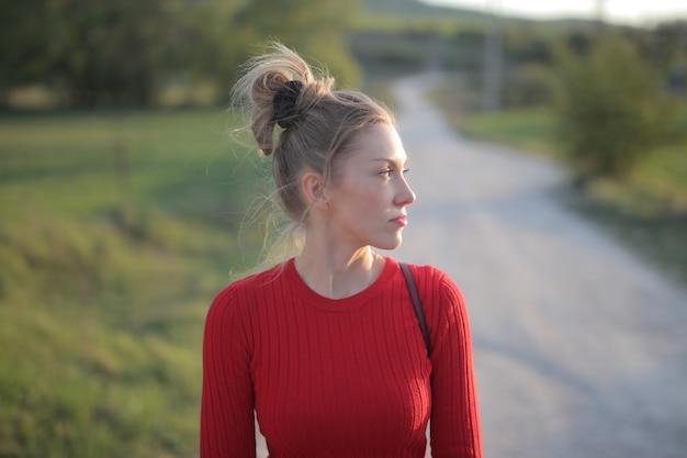 Vue d'une femme portant un chemisier rouge et profitant d'une journée ensoleillée dans la nature au bord de la route