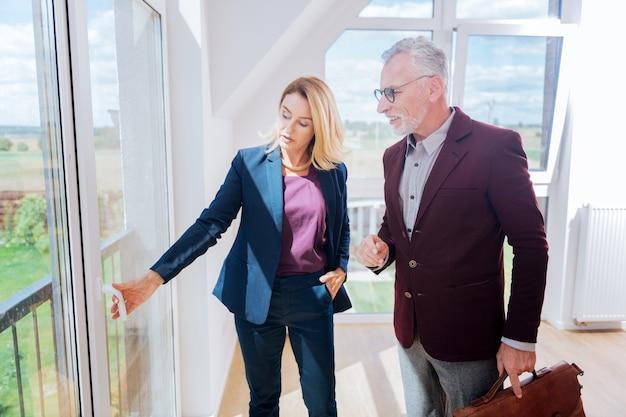 Vue de la fenêtre. agent immobilier féminin expérimenté montrant la fenêtre voir son riche client vêtu d'une veste marron très élégante