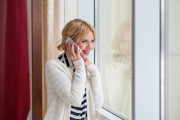 Vue de la fenêtre d'une femme séduisante appelant avec son téléphone portable tout en restant assise dans un café
