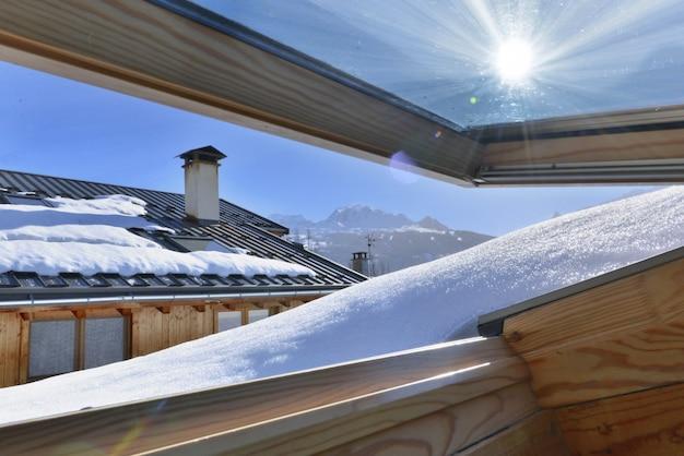 Vue d'une fenêtre s'ouvrant sur un toit recouvert de neige dans un chalet alpin