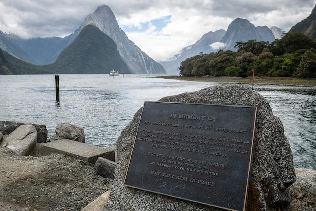 Vue sur le fjord avec des montagnes impressionnantes en toile de fond et monument en premier plan milford sound