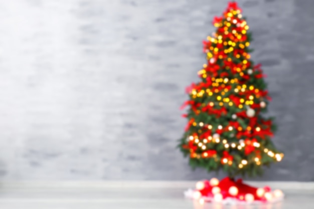 Vue floue du bel arbre de noël avec jupe sur fond de mur de couleur