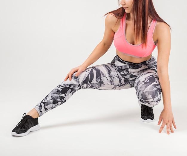 Vue frontale, de, athlétique, femme, étirage, elle, jambe