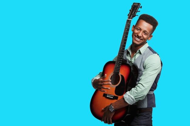 Vue frontale d'un bonheur métis jeune homme avec guitare dans ses bras, joueur sur fond bleu, espace copie