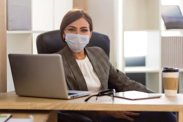 Vue frontale, de, femme affaires, à, masque facial, dans, bureau
