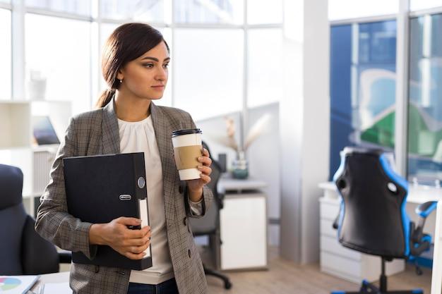 Vue frontale, de, femme affaires, tenue, café, et, classeur