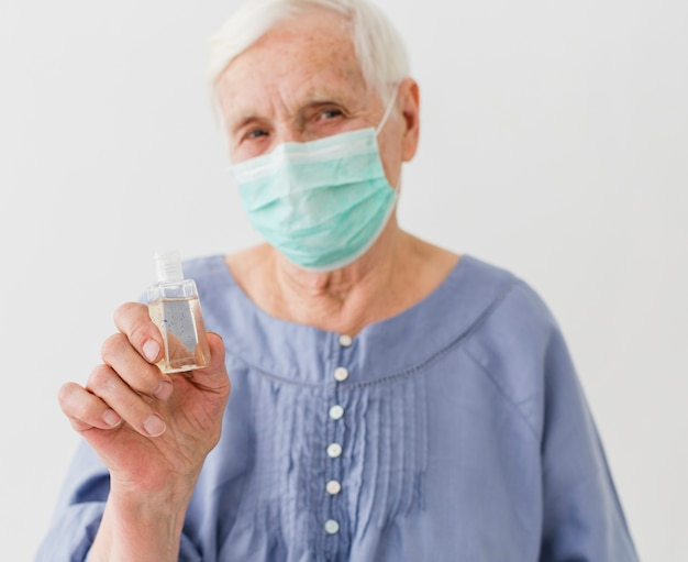 Vue frontale, de, femme aînée, tenue, désinfectant main