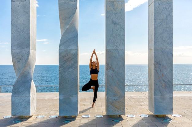 Vue frontale, de, femme américaine africaine, faire, yoga, sur, bord mer
